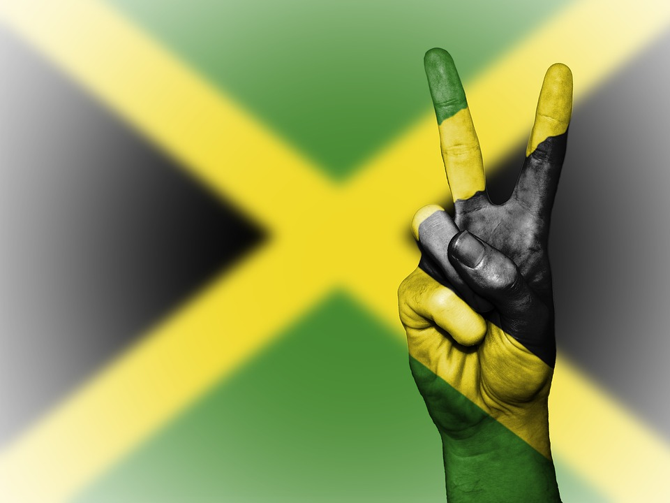 Flag of Jamaica with a hand making the sign of peace.