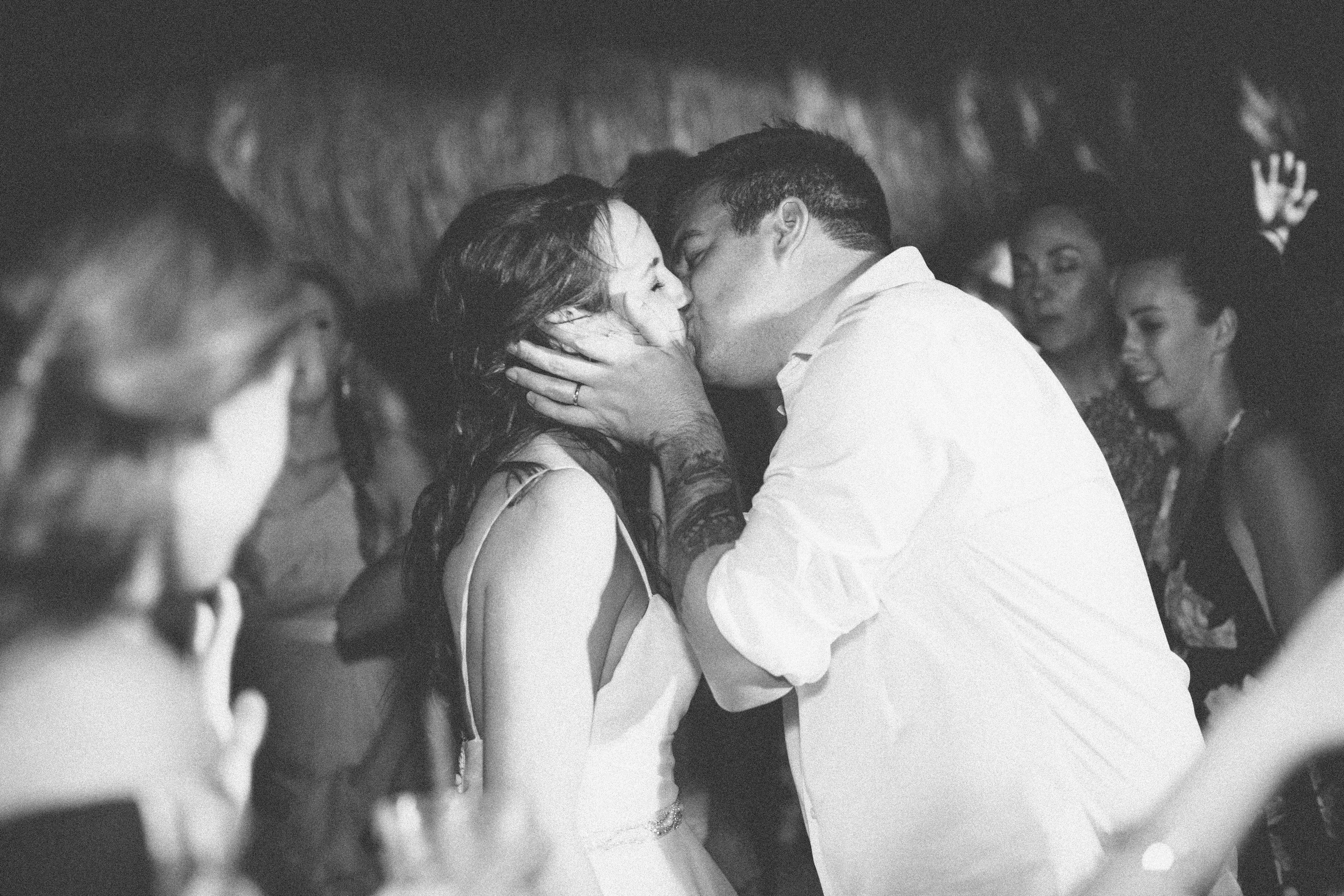Couples share a wedding reception kiss.